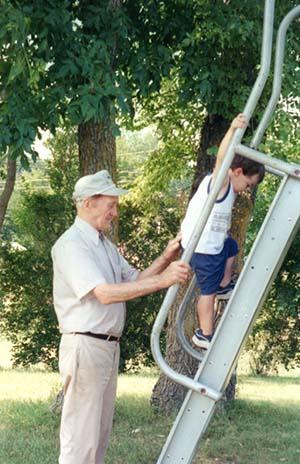 Grandparent with grandson on slide