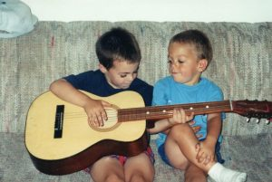 Two children playing with a guitar