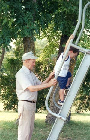 Grandparent with grandson on slide