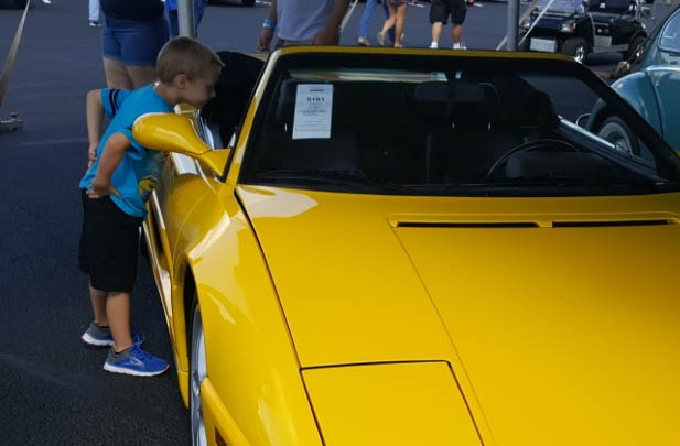 Picture of a boy looking at a car.